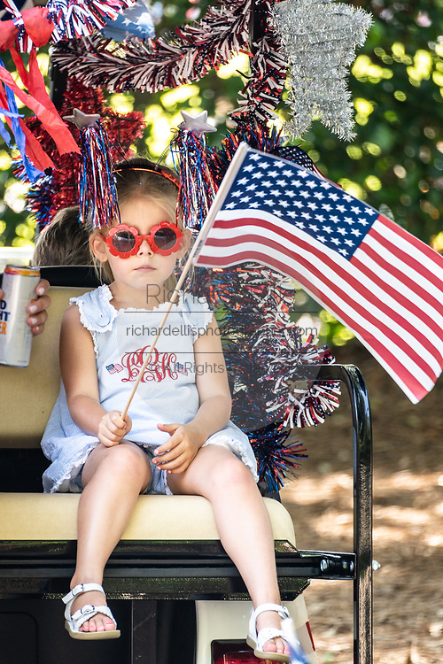Children wave flags during a golf cart  Independence Day parade despite a dramatic rise in COVID-19, coronavirus cases in Charleston County July 4, 2020 in Mount Pleasant, South Carolina. South Carolina is currently number three nationwide in number of infected per population.