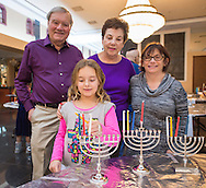 Granddaughter EMILY MIKOLA, 8, her Grandpa and Grandma BLOOMFIELD, and (at far right) their friend MARCI SILVERMAN, each get a menorah ready when the Merrick Jewish Centre attempts to regain the Guinness World's Record for Most Menorot Lit in One Place at One Time that the congregation held in 2011. On the third night of Hanukkah, the 'Light Up the Night 2 - Bringing the Record Home' event also included a ceremonial candle lighting in the main sanctuary.