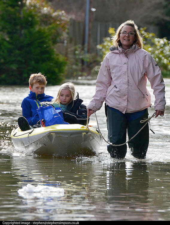 © Licensed to London News Pictures. 09/02/2014. Wraysbury, UK. Mum Vicki Schofield tows her children Callum (10) and Jessica (7) along a flooded road in a canoe. Flooding in Wraysbury in Berkshire today 9th February 2014 after the River Thames burst its banks. Photo credit : Stephen Simpson/LNP