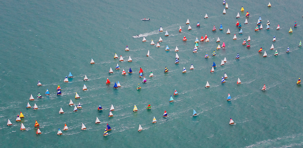 "The fleet of Seaview One Design dinghies, race in the ""75th  Anniversary Whole Fleet Race"", at the Seaview Yacht Club."