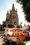 MEXICO, COLONIAL CITIES, GUANAJUATO San Miguel de Allende, the Parroquia Parish Church from the zocalo with street vendor in foreground
