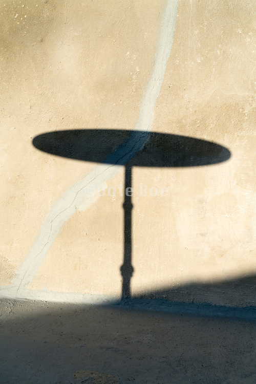 round bistro table silhouette shadow projection on a cracked wall