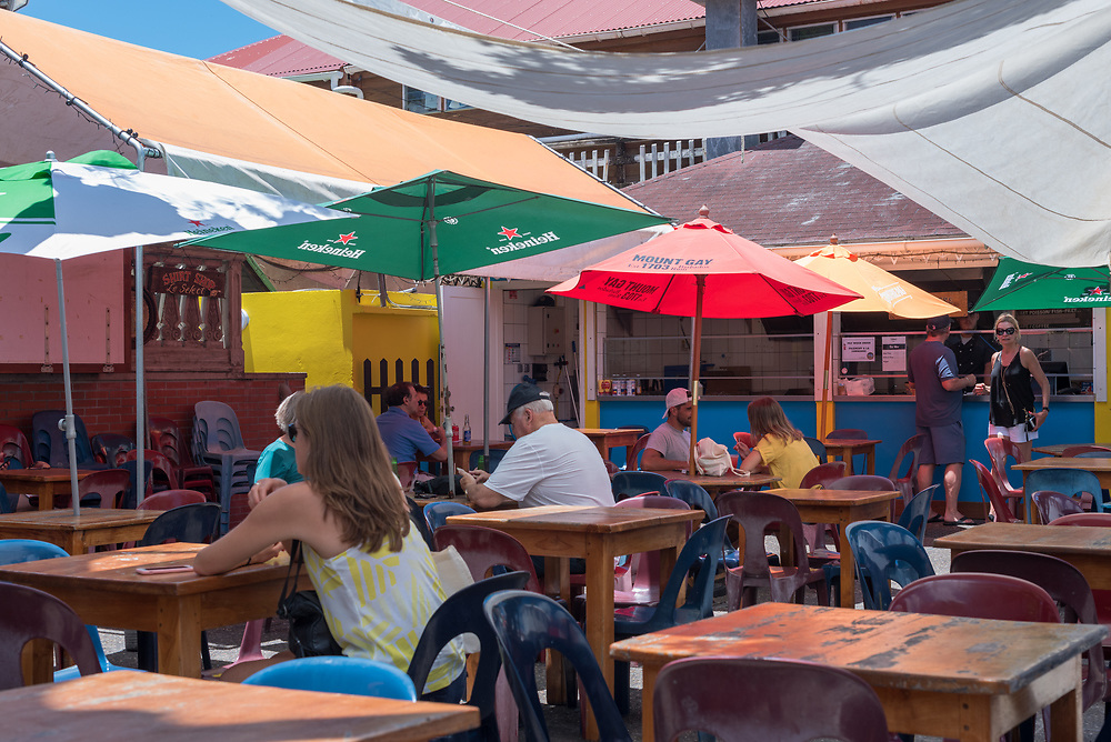 Gustavia, St Barths-- April 25, 2018. An outdoor cafe with small tables under colorful umbrellas in Gustavia, St. Barths. Editorial Use Only.