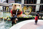 Children watch a man watering a bear made from flowers and plants located in flower art exhibition titled Flower Animal Park in Canal City shopping mall in Fukuoka City, Japan. Fukuoka is known as Japan's flower city.