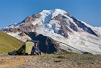 Hiker relaxing at an alpine camp on Chowder Ridge with Mount Baker (elevation 10,778 feet (3,285 m) in the distance. Mount Baker Wilderness Washington USA