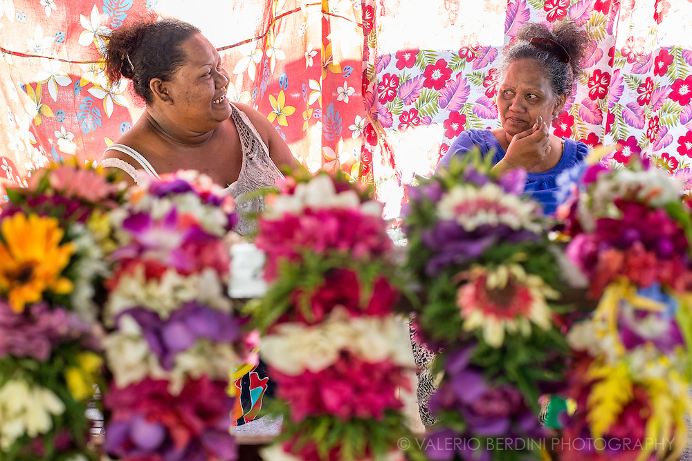 Two Polynesian women chat under the tent which is the market stall they use to sell garlands of fresh flowers.
