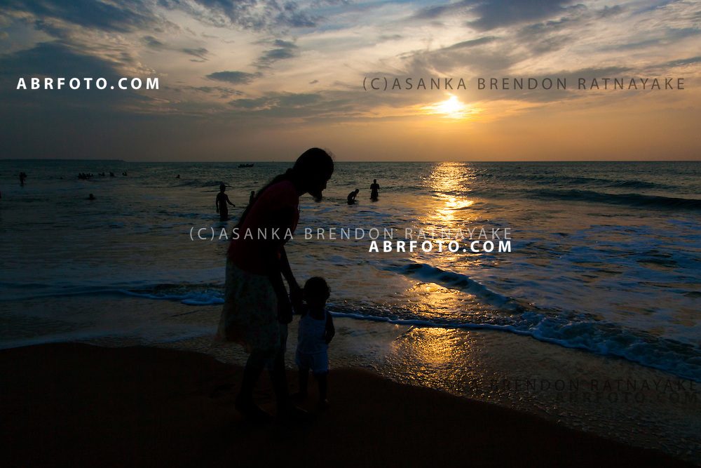 A mother and daughter (silhoutted) playing along the beach shore line in Negombo as the sunsets. Negombo is a major city in Sri Lanka, located on the west coast of the island and at the mouth of the Negombo Lagoon