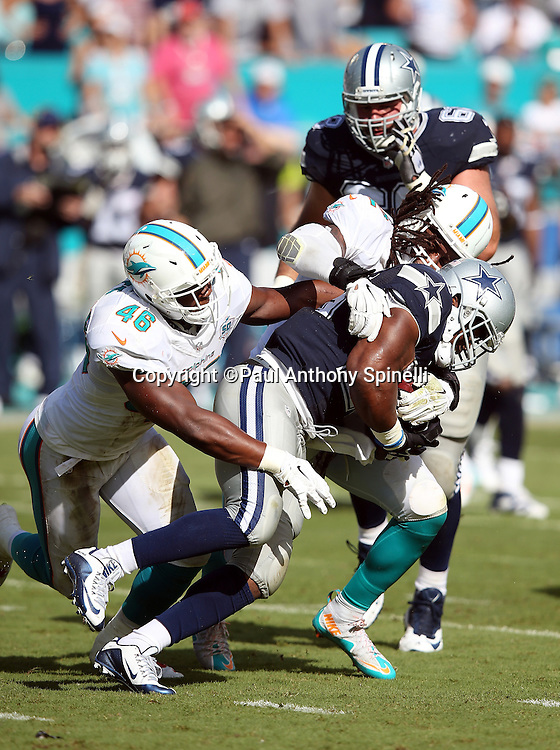 Miami Dolphins middle linebacker Kelvin Sheppard (52) and Miami Dolphins linebacker Neville Hewitt (46) gang tackle Dallas Cowboys running back Robert Turbin (23) on a second quarter run during the 2015 week 11 regular season NFL football game against the Miami Dolphins on Sunday, Nov. 22, 2015 in Miami. The Cowboys won the game 24-14. (©Paul Anthony Spinelli)