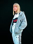 Girl wearing a grey hoodie and adidas Tracksuit bottoms