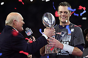 Confetti flies through the air in celebration as New England Patriots quarterback and Super Bowl LI MVP Tom Brady (12) smiles while being handed the Lombardi Trophy by former Pittsburgh Steelers Hall of Fame quarterback and FOX Sports color analyst Terry Bradshaw after the Patriots comeback win in the Super Bowl LI football game against the Atlanta Falcons on Sunday, Feb. 5, 2017 in Houston. The Patriots won the game 34-28 in overtime. (©Paul Anthony Spinelli)