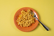 Top view of macaroni and cheese on an orange plate with fork with a yellow background.