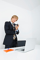 Mid adult businessman using cell phone at desk with laptop in office