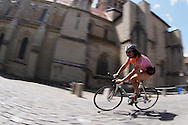 Picture by Andrew Tobin/Tobinators Ltd +44 7710 761829<br /> 04/08/2013<br /> A rider dressed in a ladies swimming costume and flower necklace shoots past the cathedral during the Cycle Messenger World Championships held in Lausanne, Switzerland. Started in 1993 by Achim Beier from Berlin, the championships are not only a sporting contest but an opportunity to unite friends and bicycle enthusiasts worldwide. The event comprises a number of challenges including a sprint, a track stand (longest time stationary on the bike), a cargo race where heavy loads are carried on special bikes, and the main race. The course winds through central Lausanne and includes bridges, stairs, cobbles, narrow alleyways and challenging hills. The main race simulates the job of a bike courier making numerous drops and pickups across the city. Riders need to check in at specific checkpoints, hand over their delivery and get a new one. The main race can take up to 4 hours for each competitor to complete.