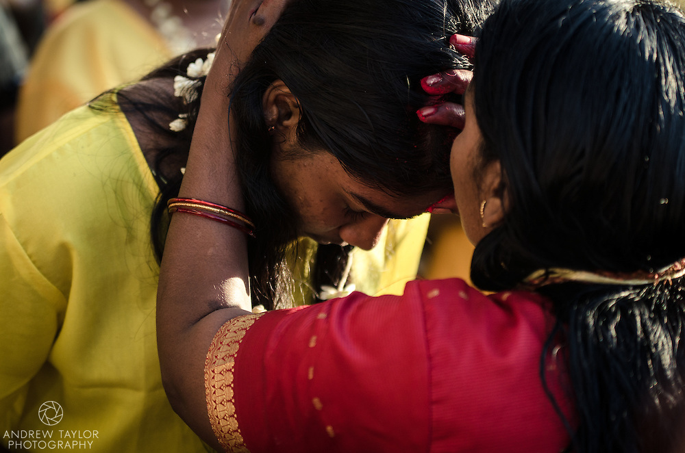 Two women share a moment after participating in  Thaipusam festival, Batu Caves, Kuala Lumpur, Malaysia