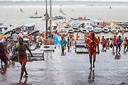 Pilgrims sheltering from the rain at Dashashwamedh Gath by the Ganges River in Varanasi, India.