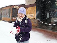 Asian Woman Making Snowball During Winter Storm, Downtown Flagstaff, Arizona