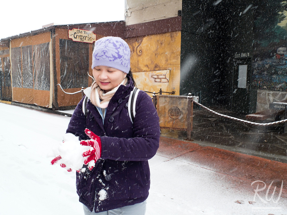 Asian Woman Making Snowball During Winter Storm, Downtown Flagstaff, Arizona