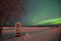 A lone phone booth sits beneath the northern lights in the Arctic Circle.