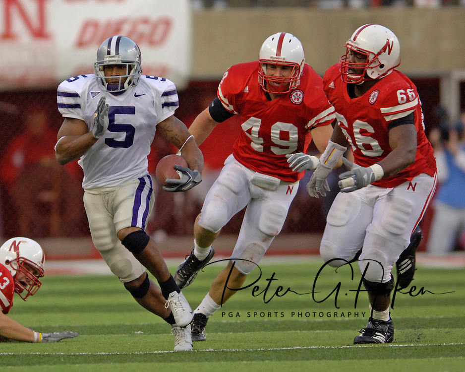 Kansas State running back Thomas Clayton (5) rushes up field for a first down in the fourth quarter, pass Nebraska defenders Adam Ickes (49) and Le Kevin Smith (66).  Nebraska defeated Kansas State 27-25 at Memorial Stadium in Lincoln, Nebraska, November 12, 2005.