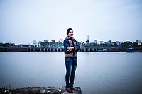 A portrait of a Vietnamese woman, standing on a ledge on the Red River in Nam Dinh town, in northern Vietnam.