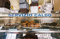 NAPLES, ITALY - APRIL 10th 2018: Cooked side dishes such as peppers, fried meat balls and fried egglplants ready to be served or to-go are seen here at the Trattoria Malinconico, a popular restaurant in the Vomero district in Naples, Italy, on April 10th 2018.<br /> <br /> Trattoria Malinconico was opened in 1953 by current owner Marianna Sorrentino's parents-in-law. At first it was only a bulk wine cellar, but then he began making a few cooked dishes – small plates that were popular with locals, which eventually morphed into larger meals. Still today the trattoria is frequented the neighborhood's older residents, many of whom have been loyal regulars for years, as well as younger locals and workers, who often stop by for a glass of wine. The menu varies from day to day, and is typically based on traditional Neapolitan recipes. Though some dishes, like meatballs, sausages, and friarielli (rapini, a type of broccoli typical to Naples), are always available.<br />  <br /> <br /> Genovese sauce is a rich, onion-based pasta sauce from the region of Campania, Italy. Likely introduced to Naples from the northern Italian city of Genoa during the Renaissance, it has since become famous in Campania and forgotten elsewhere.<br /> Genovese sauce is prepared by sautéing either beef, veal or pork in a large number of onions, for at least two but as many as ten hours. Large, cylindrical pasta like rigatoni, ziti or candele are favored because they can hold the rich sauce.