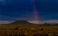 An Beautful Rainbow Appears Over The Grasslands Of New Mexico, The Old Car And Lone Tree Speak Tough Times