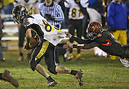 Midland's Seth Groth (85) is pulled down by Springville's Sam Scriver (3) during their game at Allison Field in Springville on Friday October 19, 2012. Midland defeated Springville 30-29.