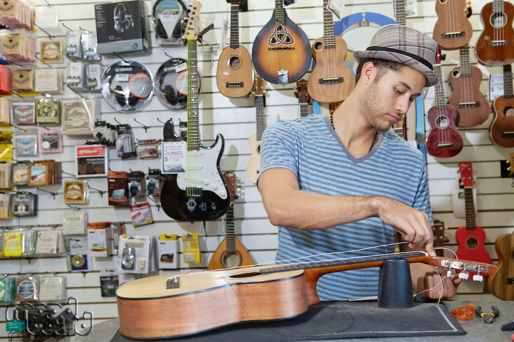 Young music store owner restringing guitar