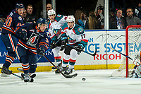 KELOWNA, CANADA - DECEMBER 29: Carson Denomie #34 of the Kamloops Blazers clears the puck out of the zone ahead of Alex Swetlikoff #17 of the Kelowna Rockets  on December 29, 2018 at Prospera Place in Kelowna, British Columbia, Canada.  (Photo by Marissa Baecker/Shoot the Breeze)