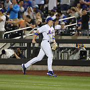 NEW YORK, NEW YORK - July 01: Brandon Nimmo #9 of the New York Mets returns to the dugout after making a catch in right field to dismiss pitcher Jason Hammel #39 of the Chicago Cubs as team mate James Loney #28 of the New York Mets watches during the Chicago Cubs Vs New York Mets regular season MLB game at Citi Field on July 01, 2016 in New York City. (Photo by Tim Clayton/Corbis via Getty Images)