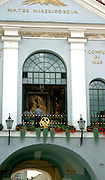 A view from the street of the interior of Ausra's Gate chapel and supplicants before the Virgin Mary; Our Lady of the Gate of Dawn; Vilnius, Lithuania