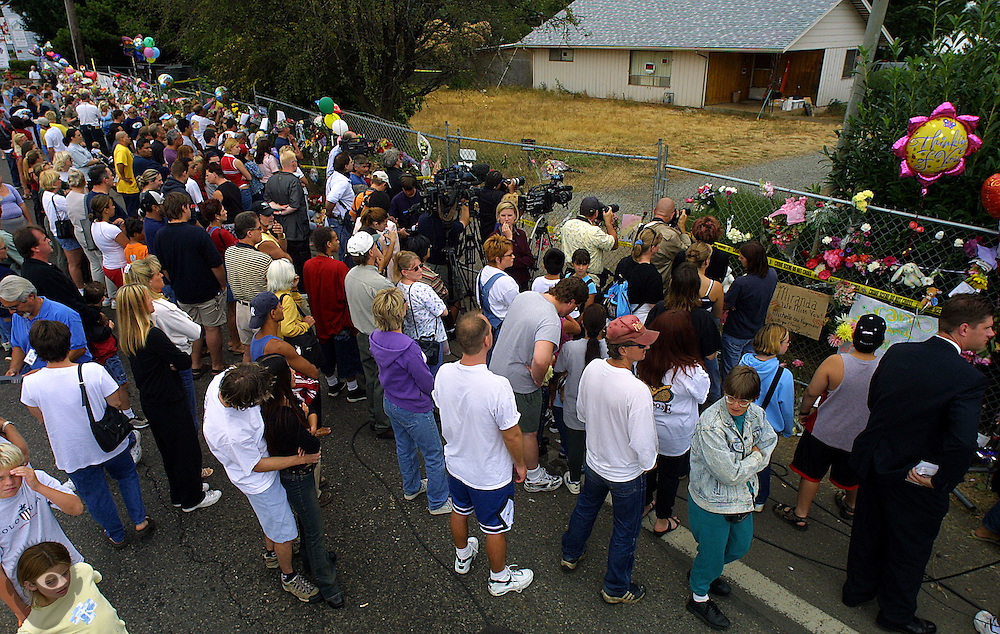 The crowd builds Sunday afternoonn outside of accused murderer Ward Weaver's property in Oregon City as police and FBI search the his yard and home. Later that afternoon a body was found buried in his under a concrete slab, the body of Miranda Daddis was confirmed.