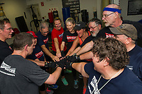 """Coach Betty Collins (lower right) brings her group into a well earned team circle high five after their """"Rock Steady Boxing"""" class at the Downtown Gym on Thursday evening. (l-r around the circle Mike O'Neill, Don Clarke, Carol Sacknoff, James St Pierre, Kate Fox, Barb Lewis, Colleen Casey, Richard Laflamme, Mike Rollins, Peter Drouin and Betty Collins.    (Karen Bobotas/for the Laconia Daily Sun)"""
