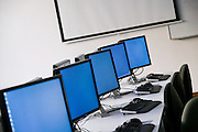 Computers lined up in a row in an empty classroom