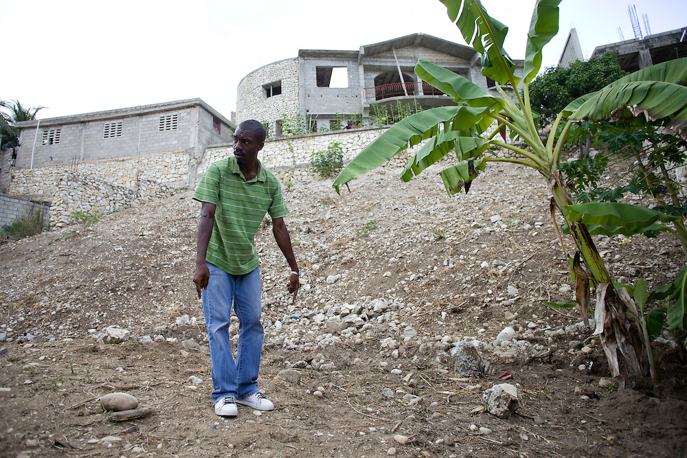 Jerome Yves Marie points out where OXFAM has said they will build latrines on this piece of land that Marie say's his uncle who lives in Florida gave him permision to move to with the other families who are in the camp of 44 families on private land. Armed men came in May and threatened the residents that if they did not vacate the property in two weeks they would be shot. Two months later the families are still in the same place but are hoping to move soon to this new piece of land.
