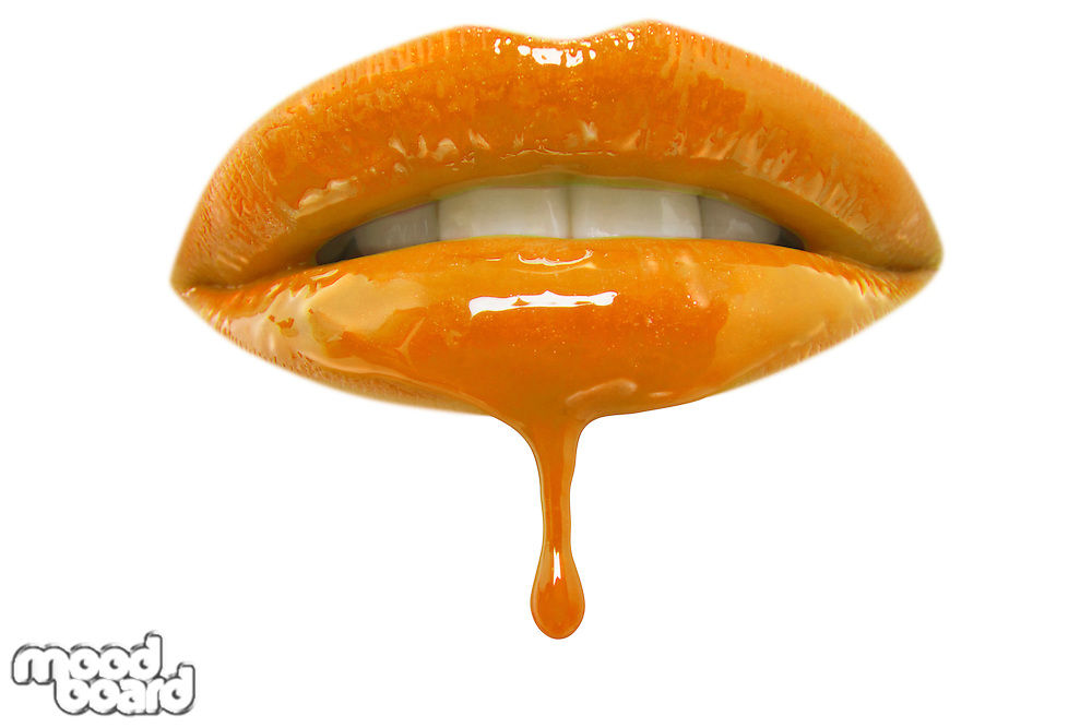 Close-up of orange lip-gloss dripping from woman's lips over white background