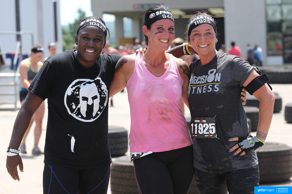 Dashann Pontes, (left), Kendra Martelle, (centre) and Jennifer Ward, at the tyre lift obstacle during the Reebok Spartan Race. Mohegan Sun, Uncasville, Connecticut, USA. 28th June 2014. Photo Tim Clayton
