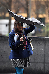 Londoners attempt to stay dry under umbrellas as strong winds and rain continue to affect the UK. <br /> Tuesday, 11th February 2014. Picture by Ben Stevens / i-Images
