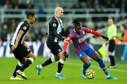 Wilfried Zaha (#11) of Crystal Palace defends the ball from the challenge of Jonjo Shelvey (#8) of Newcastle United during the Premier League match between Newcastle United and Crystal Palace at St. James's Park, Newcastle, England on 21 December 2019.