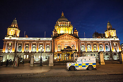 © Licensed to London News Pictures . 09/01/2013 . Belfast , UK . An armoured police vehicle parked in front of Belfast City Hall this evening (9th January 2013) . On 3rd December , councillors voted to limit the number of days the Union Jack flag would be flown , sparking weeks of violence . Photo credit : Joel Goodman/LNP