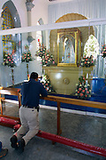 Man praying to Nuestra Señora del Valle (Virgin Mary) statue at the Basilica Nuestra Señora del Valle.