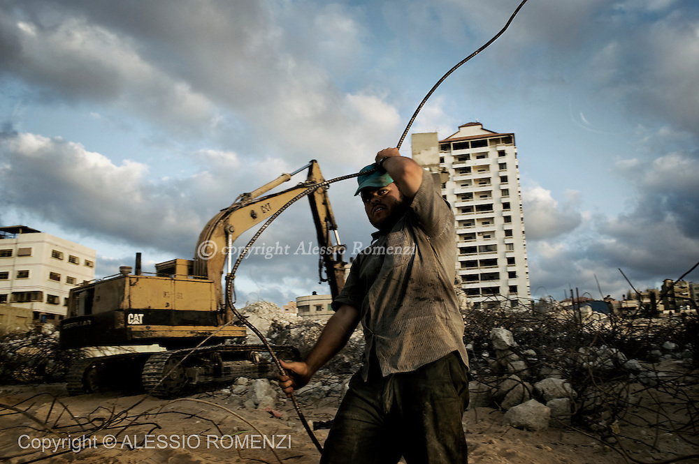 GAZA CITY : A Palestinian worker while collecting scrap material from the rubble of a hotel along the Gaza City waterfront on October 25, 2010. Buildings damaged incurred during different waves of unrest have brought a new industry of recovering metal rods and cement, obtained through the grinding of concrete blocks, to supply the chronic lack of building material throughout the Strip, which is under Israeli partial closure.© ALESSIO ROMENZI