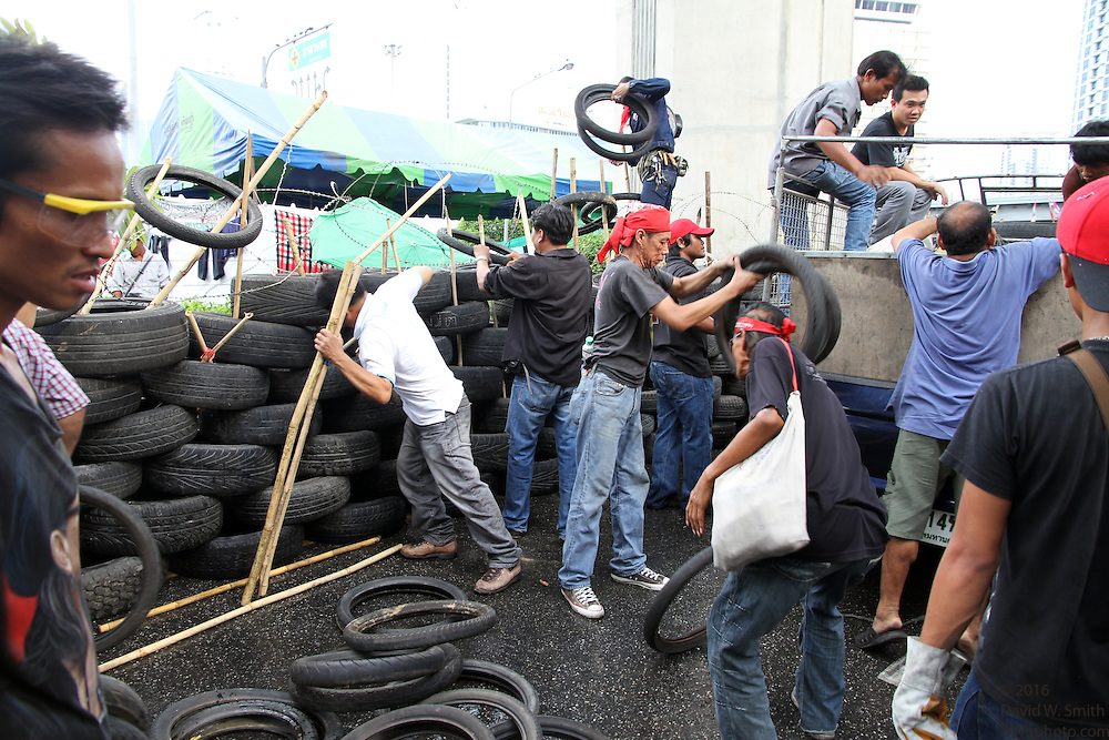 Protestors unload tires used for a barricade during the Red Shirts anti-government protest in the Silom area of Bangkok.