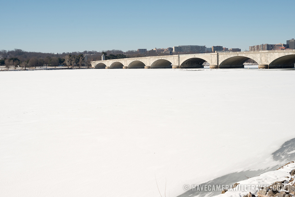 Arlington Memorial Bridge spans an expanse of ice and snow-covered Potomac from Washington DC across to Arlington Virginia. The Potomac running through Washington DC is frozen and covered with a layer of snow. The region has experienced an unusually cold winter, with sustained low temperatures.