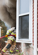 A firefighter pulls a firehose through the door of a burning home.