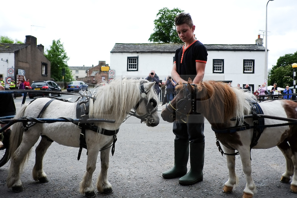 © Licensed to London News Pictures. <br /> 05/06/2014. <br /> <br /> Appleby, Cumbria, England<br /> <br /> A young boy stands with two small horses as gypsies and travellers gather during the annual horse fair on 5 June, 2014 in Appleby, Cumbria. The event remains one of the largest and oldest events in Europe and gives the opportunity for travelling communities to meet friends, celebrate their music, folklore and to buy and sell horses.<br /> <br /> The event has existed under the protection of a charter granted by King James II in 1685 and it remains the most important event in the gypsy and traveller calendar.<br /> <br /> Photo credit : Ian Forsyth/LNP