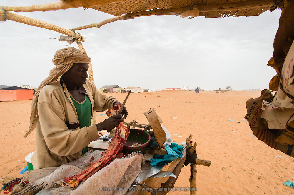 A man selling meat at the Mbera refugee camp for Malian refugees in southeastern Mauritania on 2 March 2013. Animals are herded to a livestock market in nearby Mbera village and sold to meat vendors who slaughter them and sell meat by the kilo for a modest profit to those who can afford it.