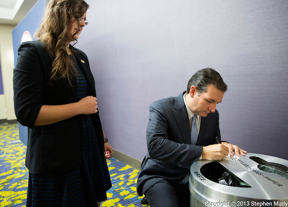 DES MOINES, IA - OCTOBER 25, 2013: Senator Ted Cruz, Republican of Texas, kneels by a trashcan in the corner as he signs a program for Sarah Brooks (left), 19, of Des Moines, Iowa before the start of the Iowa GOP Ronald Reagan Dinner at the Iowa Events Center - Community Choice Credit Union Convention Center in Des Moines, Iowa.