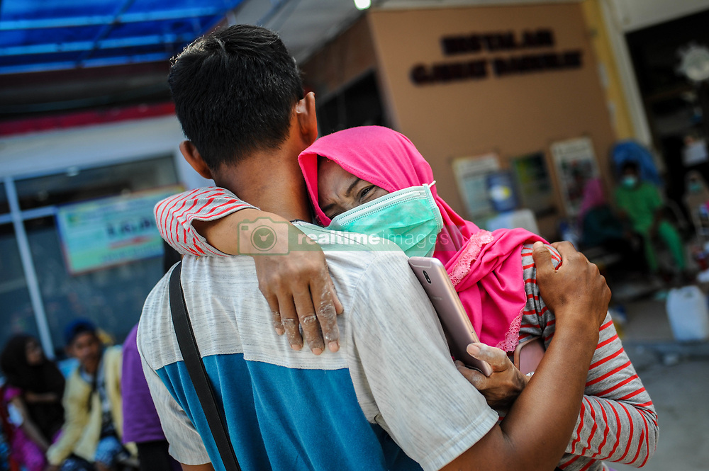 October 4, 2018 - Palu, Central Sulawesi, Indonesia - A woman cries when she met her relatives at Anutapura Hospital after the earthquake. A deadly earthquake measuring 7.7 magnitude and the tsunami wave caused by it has destroyed the city of Palu and much of the area in Central Sulawesi. According to the officials, death toll from devastating quake and tsunami rises to 1,347, around 800 people in hospitals are seriously injured and some 62,000 people have been displaced in 24 camps around the region. (Credit Image: © Hariandi Hafid/SOPA Images via ZUMA Wire)
