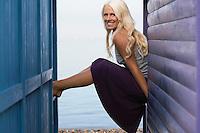Woman sitting on balustrades of beach house verandahs portrait